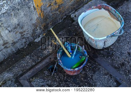 The dirty paint brush was soaked in a bucket of water to wash it off.