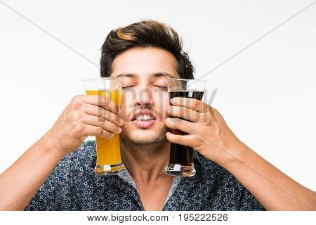 Young handsome Indian man in casual shirt holding two glasses of fresh orange juice and dark aerated drink for breakfast or for refreshment