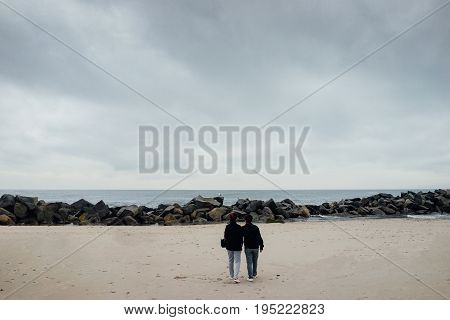 The Couple Stand And Look Out From The Beach.