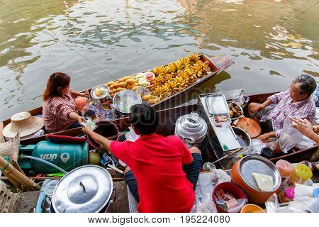 RATCHABURI THAILAND - MARCH 20 : Local vendors selling goods at Damnoen Saduak Floating Market near Bangkok in Thailand on March 20 2016. Damnoen Saduak is a very popular tourist attraction.