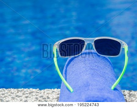 Sunglesses and blue towel at the side of swimming pool. Vacation beach summer travel concept