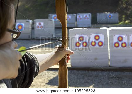 Archery or shooting range with bow and arrows on a sunny outdoor setting. The equipment is used in competitive sports and as a traditional weapon. The circular targets are what the archer shoots.