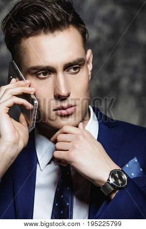 Portait of a serious businessman on his phone.