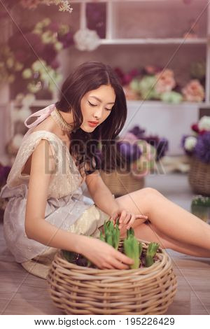 Beautiful girl in tender white dress sitting on the floor against floral background in flower shop. Joyful asian female florist. Playful fashion model looking and touching many spring flowers.