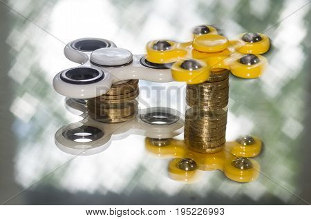 Spinners located on a stack of shiny coins mirror rotate shimmering light background.