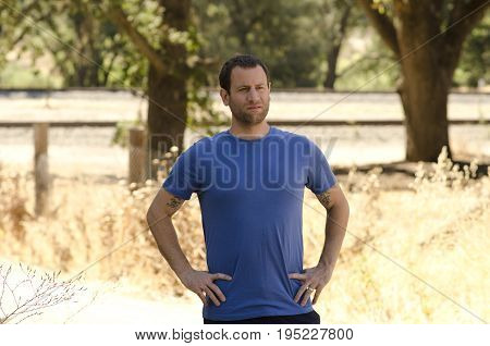 Man alone with hands on his hips in a natural outdoor setting, with trees and train tracks in the background.