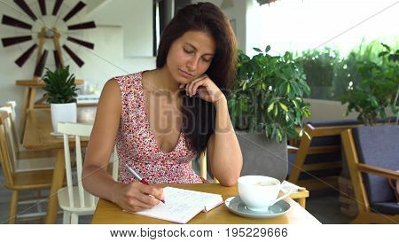 Young woman writer writes a book in cafe. Female writing in notepad