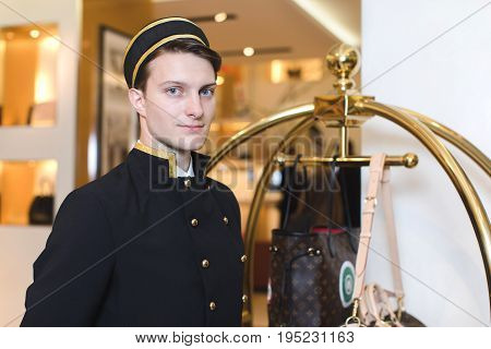 Smiling man in bellboy uniform standing with luggage cart and looking at camera