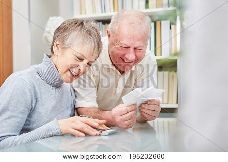 Senior with cash book and receipts doing accounting with wife