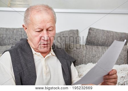 Senior man with finance bill for taxes paperwork