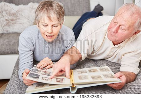 Senior couple in relaxation holding photo album