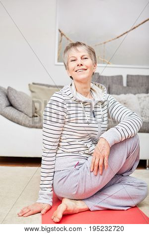 Senior citizen making stretching fitness exercise at home