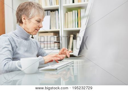 Senior woman surfing the internet with computer at home office