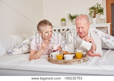Senior citizens having breakfast in bed in romantic holiday get away