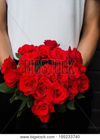 Male Person Holding A Beautiful Bouquet Of Red Roses Wearing White Shirt And Black Pants Against A G