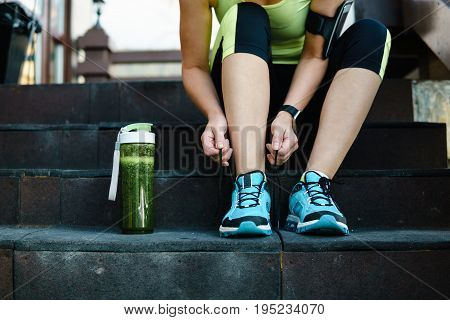 Green Detox Smoothie Cup And Woman Lacing Running Shoes Before Workout.