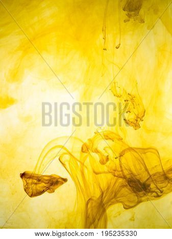 Ink swirl in a water on yellow background. The paint splash in the water. Soft dissemination a droplets of colored ink in water close-up. Abstract background. Explosion of color splashes acrylic ink.