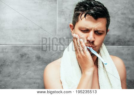 Toothache. Frustrated young handsome man touching his cheek while brushing teeth in bathroom. sensitive teeth and gums. Dental hygiene, health care, beauty and people concept.