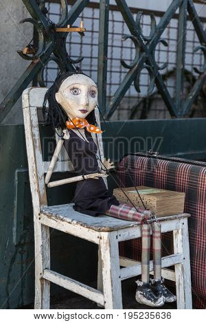 Wooden Worn-out Woman Marionette on White Chair