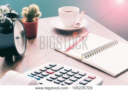 Calculator notebook coffee on table Accounting workspace concept