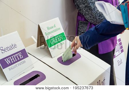 Melbourne, Australia - July 2, 2016: a woman placing a ballot paper in a ballot box on 2016 federal election day.