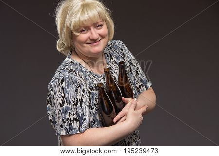 Lonely poor fat woman aged drinking beer and eating fish.