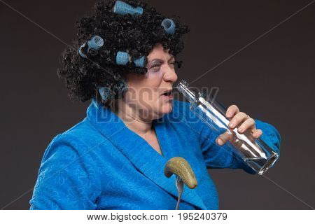 Lonely middle-aged woman is drinking from a glass tumbler of vodka and eating pickles