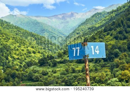 Rusty kilometer marker with beautiful mountains on the background