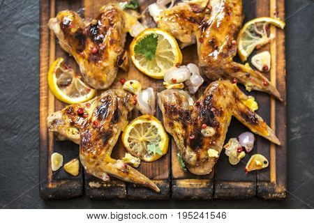 grilled chicken wings with lemon and greens on a dark background
