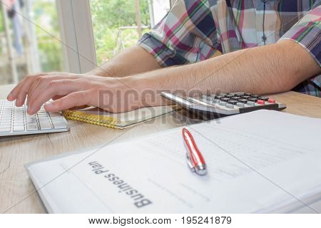 Close up view of bookkeeper or financial inspector hands making report calculating or checking balance. Business plan calculator on the table