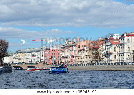 SAINT PETERSBURG RUSSIA - MAY 3 2017: Unknown tourists are on excursion boats on Fontanka River near Anichkov Bridge St. Petersburg Russia