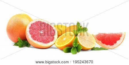 Several kinds of multi-colorful, whole and cut citrus: sour, juicy lemons, ripe, fresh grapefruits, and sweet oranges with bright green leaves of mint, isolated on a white background. Vitamin C.