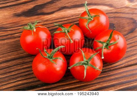Close-up fresh vegetables for a salad. Ripe, juicy, fresh and bright red tomatoes with green leaves on a dark wooden table background. Fresh and ripe cherry tomatoes on a wooden table.