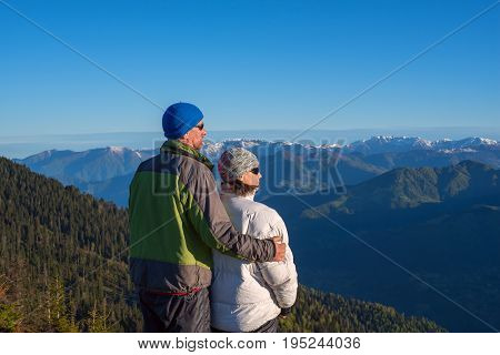 Happy Couple Of Travelers Is Admiring The Dawn In The Mountains