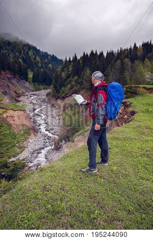 Traveler With Map On Shore Of A Mountain River