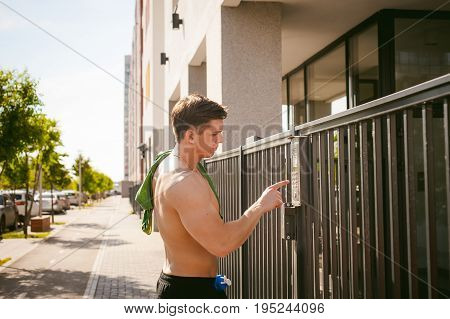 Handsome Sexy Male Athlete Man With Naked Torso, Stands Near Gate, Calling Intercom To Open Door, Af