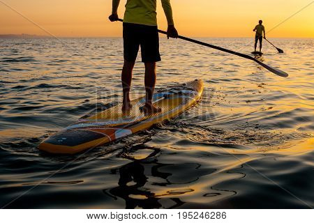 SUP silhouette two man standing with a paddle on the surfboard at sunset stand up paddle boarding legs