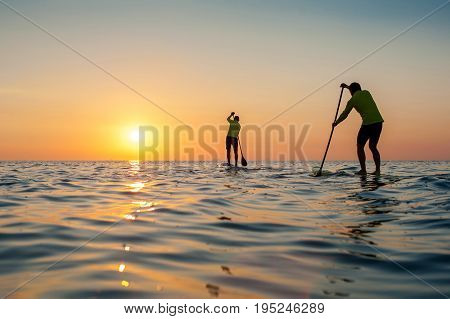 SUP silhouette two man standing with a paddle on the surfboard at sunset stand up paddle boarding meet the sun
