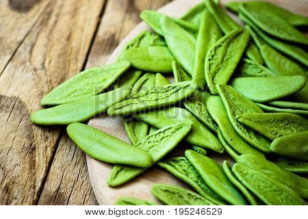 Green spinach italian pasta in the shape of olive leaves scattered on wooden plate mediterranean cuisine healthy diet