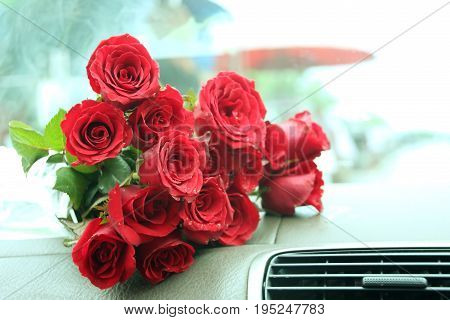 Beautiful red roses bouquet on car console.