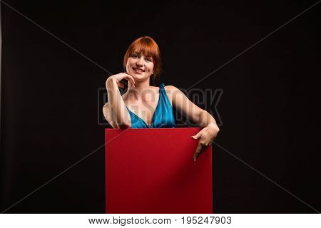 Young cheerful woman portrait of a confident businesswoman showing presentation, pointing placard black background. Ideal for banners, registration forms, presentation, landings, presenting concept.