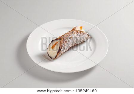 Round dish with Sicilian cannoli isolated on grey background