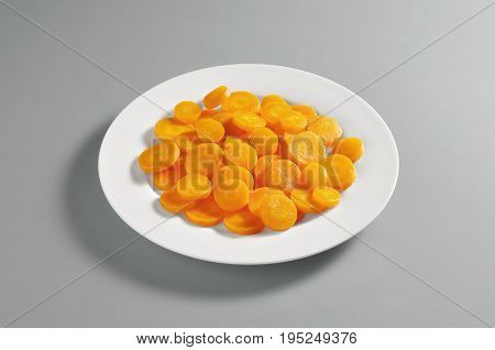 Round dish with a portion of sliced boiled carrots isolated on grey background
