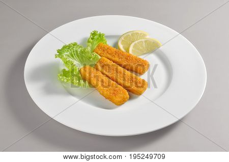 Round dish with fillet fish sticks breaded and fried isolated on grey background