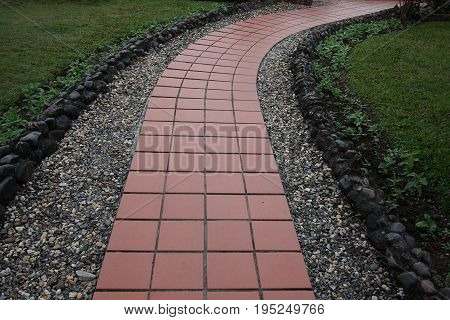 Clay tile and gravel walk path on green grass