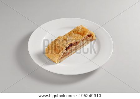 Round dish with strudel slice isolated on grey background