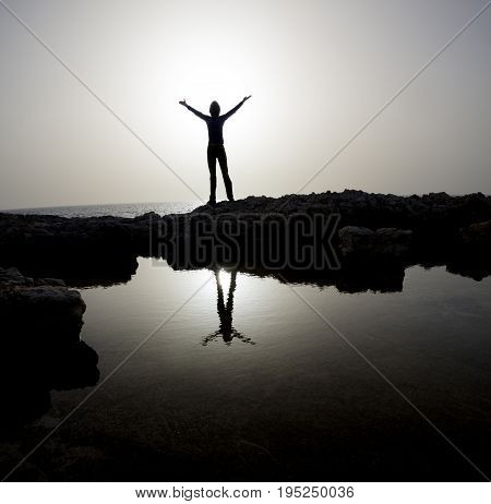 Woman's silhouette with outstretched hands situated in rock between sea and puddle. Dusk.
