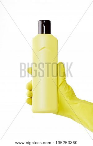 Hand in a rubber yellow glove holds a bottle of liquid detergent on a white background. cleaning