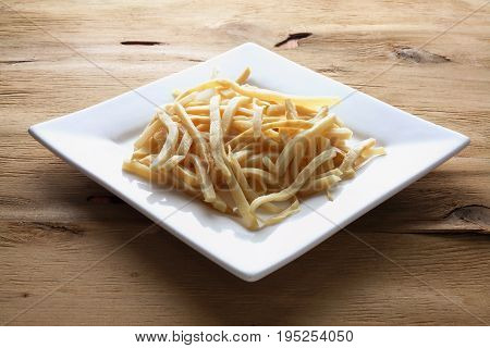 Potato Chips on Plate on Wooden Background