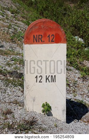 Red and white milestone on highway NR.12 with text 12 KM.